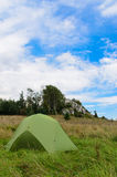 Pitched tent in meadow with big rock in background Royalty Free Stock Images