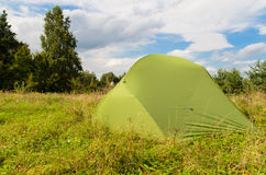 Pitched tent in meadow on sunny day Stock Photos