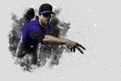 Pitcher Baseball. Player with a blue uniform coming out of a blast of smoke Royalty Free Stock Photography