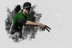 Pitcher Baseball. Player with a green uniform coming out of a blast of smoke Royalty Free Stock Photography