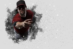Pitcher Baseball. Player with a red uniform coming out of a blast of smoke Royalty Free Stock Image