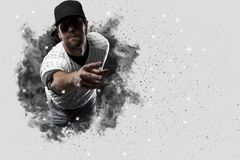 Pitcher Baseball. Player with a white uniform coming out of a blast of smoke Stock Photography