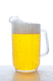 Pitcher of Beer on Wet Counter Top. Pitcher of beer on a wet bar counter top. Vertical format over white royalty free stock images
