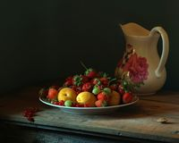 Pitcher and berries. Still life with pitcher and fruit on table Royalty Free Stock Photos