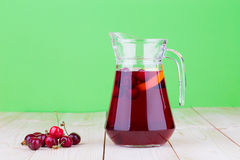 Pitcher with cherries and juice Royalty Free Stock Image