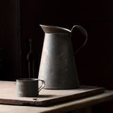 Pitcher and Cup. Vintage metal pitcher and cup composed with natural light Stock Images