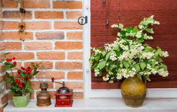 Pitcher with flowers. Jug with jasmine flowers on a background of blinds and brick wall. interior, kitchen Stock Images