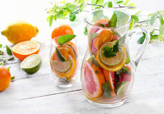 Pitcher and glass with citrus fruits Royalty Free Stock Photography