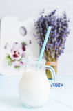 Pitcher glass of milk with lavender and cocktail tube on a blue wooden background instagram filter Stock Photo