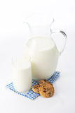 Pitcher and glass with some milk and cookies. On white Royalty Free Stock Image