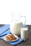 Pitcher and glass with some milk and cookies. On wood Stock Photos