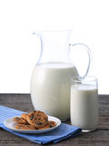 Pitcher and glass with some milk and cookies. On wood Royalty Free Stock Photos