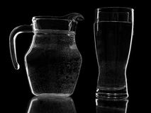 Pitcher and glass. Pitcher and a glass of water on a black background Stock Image