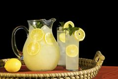 Pitcher And Glasses Of Cold Fr. Esh Squeezed Lemonade On Rattan Tray ~ Isolated On Black Royalty Free Stock Photography