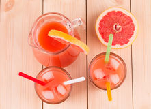 Pitcher and glasses full of grapefruit juice. Royalty Free Stock Photos
