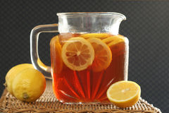 Pitcher of Ice Tea and Lemons. Glass pitcher of ice tea with lemon slices Royalty Free Stock Image