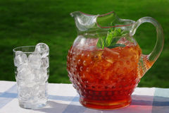 Pitcher of Iced Tea. An antique Hobnail Pitcher full of Iced Tea with a sprig of mint. A glass full of ice sits along side, in the afternoon sun Royalty Free Stock Image