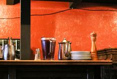 Pitcher of iced tea and coffee pot and salt and peper on sideboard against rustic orange wall. A Pitcher of iced tea and coffee pot and salt and peper on Royalty Free Stock Photos