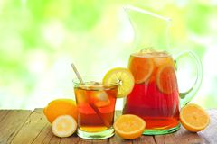 Pitcher of iced tea with glass and defocused outdoors background Stock Images