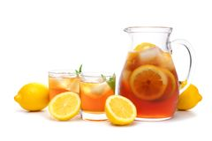 Pitcher of iced tea with two glasses isolated on white. Pitcher of iced tea with two glasses and lemons isolated on a white background Royalty Free Stock Images