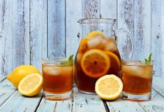 Pitcher of iced tea with two glasses on rustic blue wood. Pitcher of iced tea with two glasses and lemons on rustic blue wood background Royalty Free Stock Photography