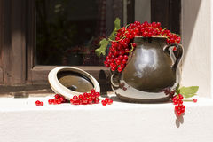 Pitcher/jug of redcurrant on a direct sunlight on a window royalty free stock photography