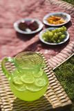 Pitcher of lemonade. Green plastic pitcher of lemonade and lemons with a picnic spread out in the background Stock Images