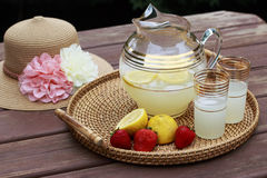 Pitcher of Lemonade and glasses with fruit. Pitcher of Lemonade, Sun Hat, Fruit and glasses on a table Royalty Free Stock Photography