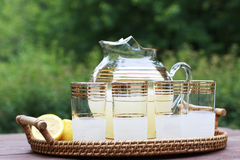Pitcher of Lemonade and glasses. Pitcher of Lemonade, glasses, and lemons on a wooden table Stock Photography
