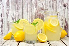 Pitcher of lemonade with glasses on rustic white wood. Pitcher of lemonade with two glasses and lemons on rustic white wood background Stock Photo