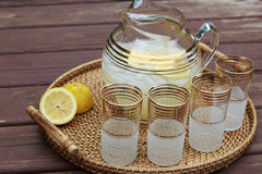 Pitcher of Lemonade and glasses on a table. Pitcher of Lemonade and four glasses on a wooden table Royalty Free Stock Photo