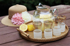Pitcher of Lemonade and glasses on a table. Pitcher of Lemonade, sun hat, and glasses on a wooden table Stock Images