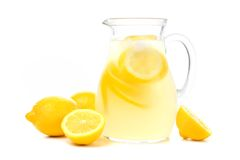 Pitcher of lemonade with lemons isolated on white. Pitcher of lemonade with lemons isolated on a white background Stock Photos