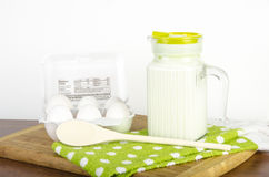 Pitcher of Milk with a carton of eggs with whisk. Pitcher of Milk, half a dozen eggs in carton showing nutritional value and whisk on a table with cutting board Stock Photos