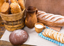 Pitcher, milk and fresh bread on table Royalty Free Stock Image