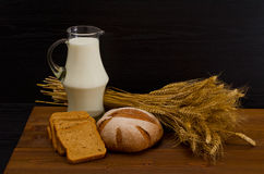Pitcher of milk, round rye bread, a sheaf of wheat, bread slices on a wooden table Royalty Free Stock Photo