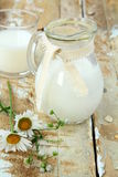 Pitcher of milk on a wooden table Stock Photos