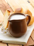 Pitcher of milk on a wooden table Stock Photography