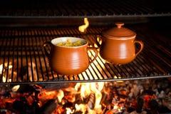 Pitcher mit Nahrung auf Feuer lizenzfreies stockfoto
