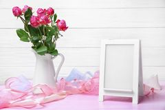 Pitcher with roses and empty frame. On table Stock Images