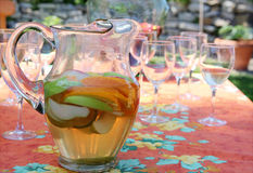 Pitcher of sangria. A pitcher of refreshing white sangria against a festive table scape Royalty Free Stock Photo