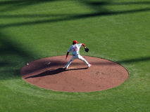Pitcher steps forward to throw pitch from mound Stock Photography