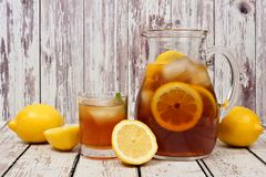 Pitcher of summer iced tea with glass on rustic white wood. Pitcher of summer iced tea with a glass and lemons on rustic white wood background Stock Image