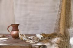 Pitcher on a table with a fishing net. Skein of white thread and an earthenware jug on the table stock photos