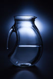 Pitcher of water. With blue background. Studio shot Royalty Free Stock Photography
