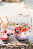 Pitcher with water, berries and  ice cubes on table over garden terrace background. Home scene Stock Photos