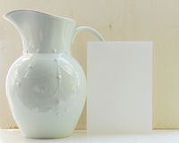 Pitcher with white paper. Teal vintage-style pitcher with white announcement paper against rough wood grain backdrop Royalty Free Stock Photography