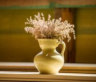 pitcher with wildflowers is standing on a wooden table in the room. stock photography
