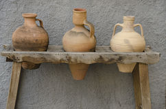 Pitchers. Three pottery pitchers on a wooden stand Stock Photography