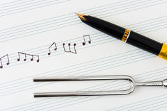 Pitchfork and pen on music sheet royalty free stock photography
